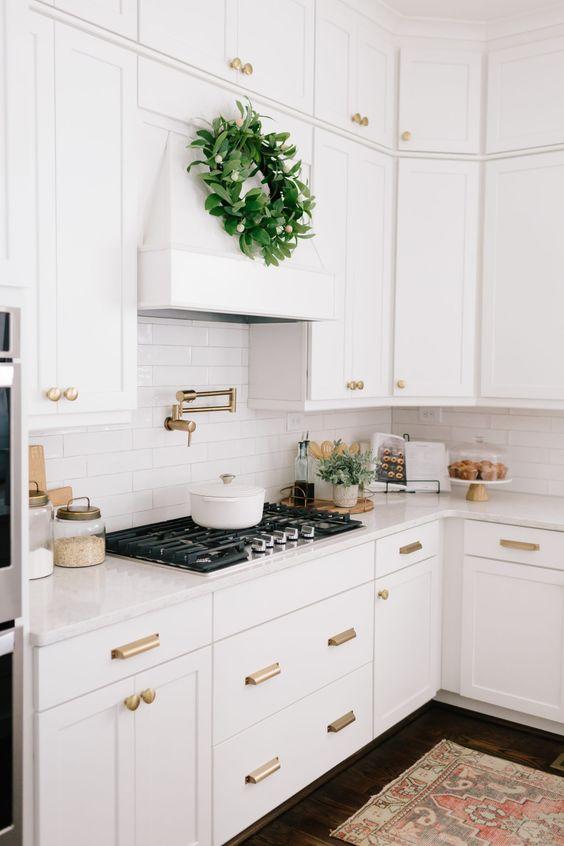 a white farmhouse kitchen with shaker style cabinets, white quartz countertops and a white skinny tile backsplash plus brass fixtures