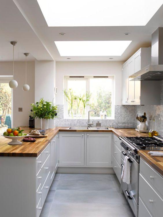 a white kitchen with butcherblock countertops, mosaic tiles and skylights is a very airy and welcoming space