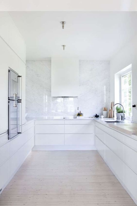 a white minimalist kitchen with a white stone backsplash plus countertops is a very airy and serene space