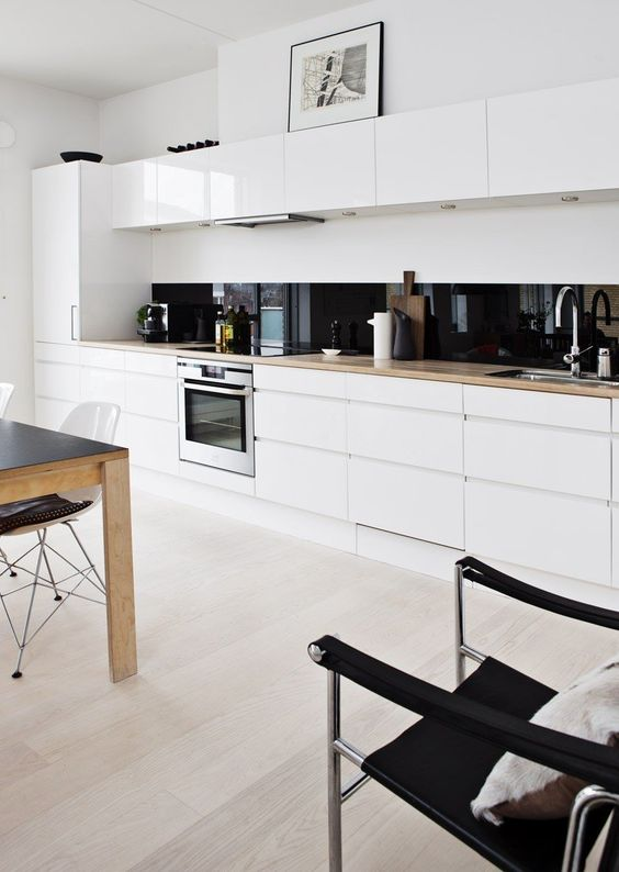 a white minimalist one wall kitchen with blonde butcherblock countertops, a black glass backsplash and an eating zone