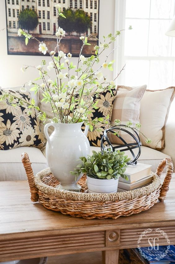 a white vase with greenery and blooming branches can be used as a simple spring centerpiece