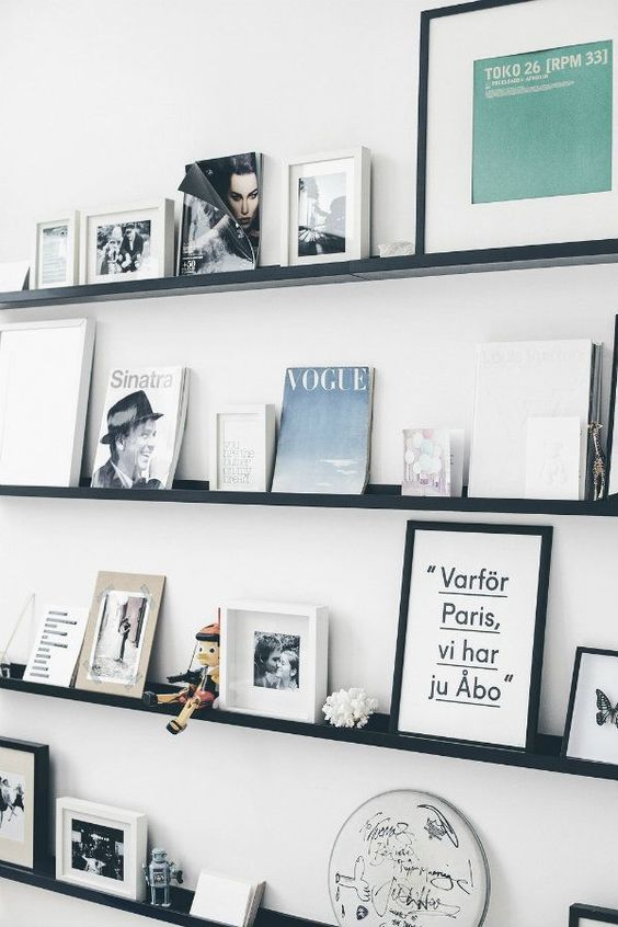 a white wall and contrasting black ledges, books, artworks, decorative plates and even funny toys personalize the space a lot