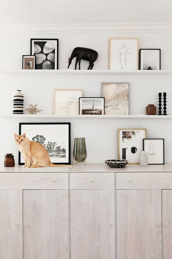 a white wall with white ledges and very stylish art in mismatching frames, vases, candleholders and lovely statuettes
