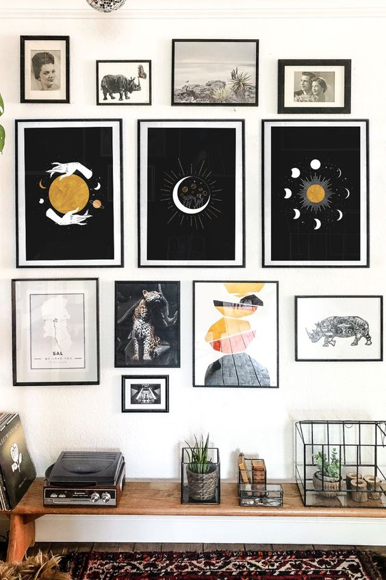 a witchy gallery wall with thin black frames, bold prints, vintage artworks and photos is a catchy idea