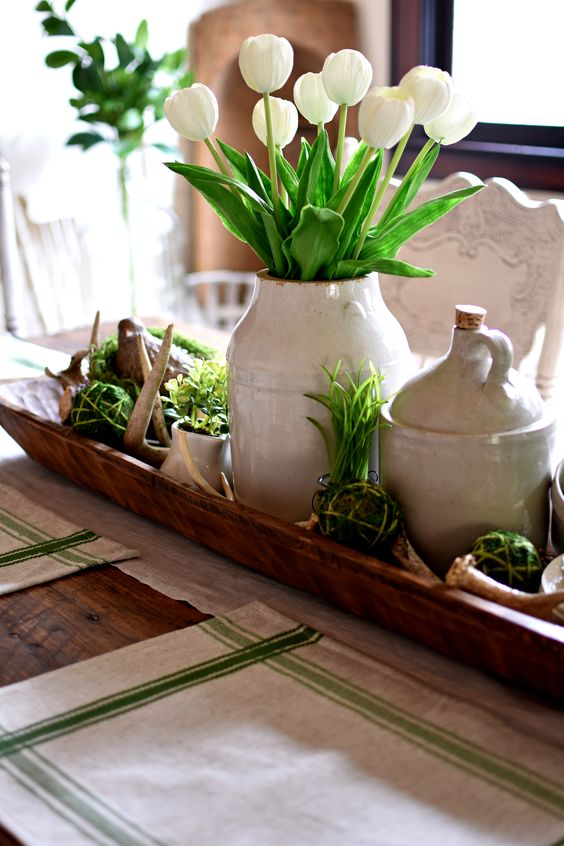 a wooden box with moss balls, grass and greenery, a vase with white tulips and antlers for a rustic spring table