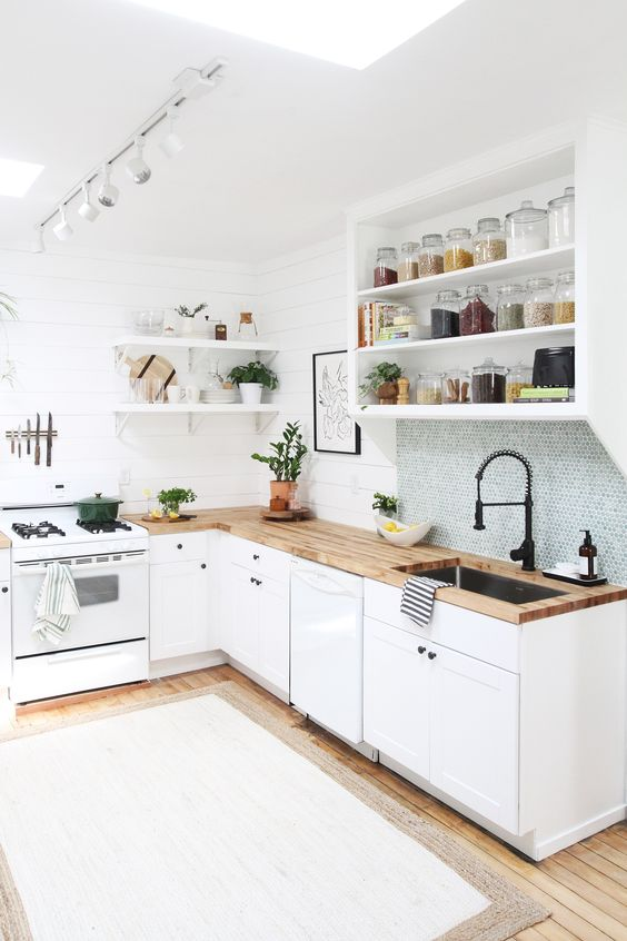 an L shaped kitchen in white, with butcherblock countertops and a skylight plus a blue penny tile backsplash