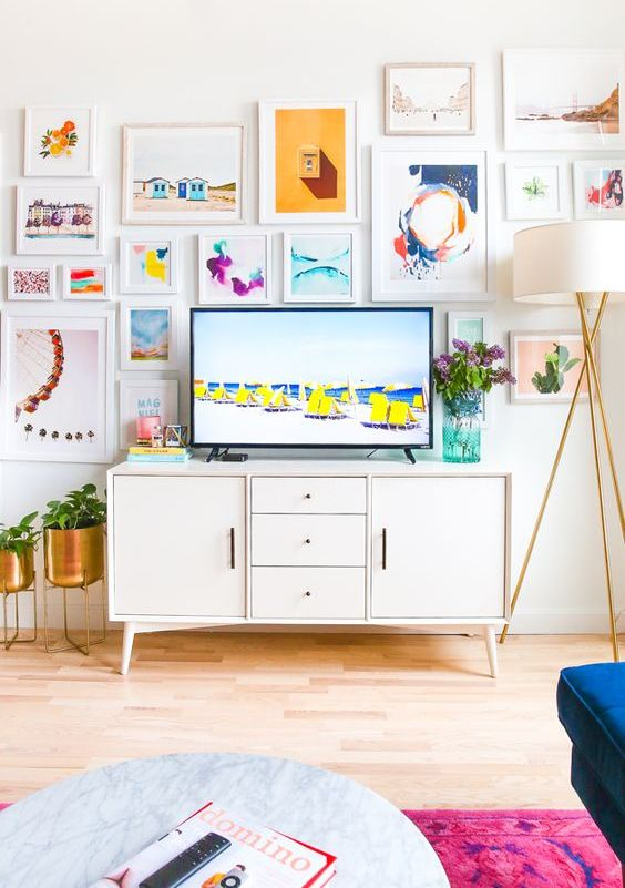 an airy and cool gallery wall with bright prints and watercolors and white frames includes a TV and makes the space bolder