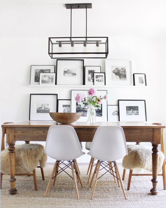 an airy gallery wall with white ledges, black and white artworks in black and white frames perfectly matches a Nordic space