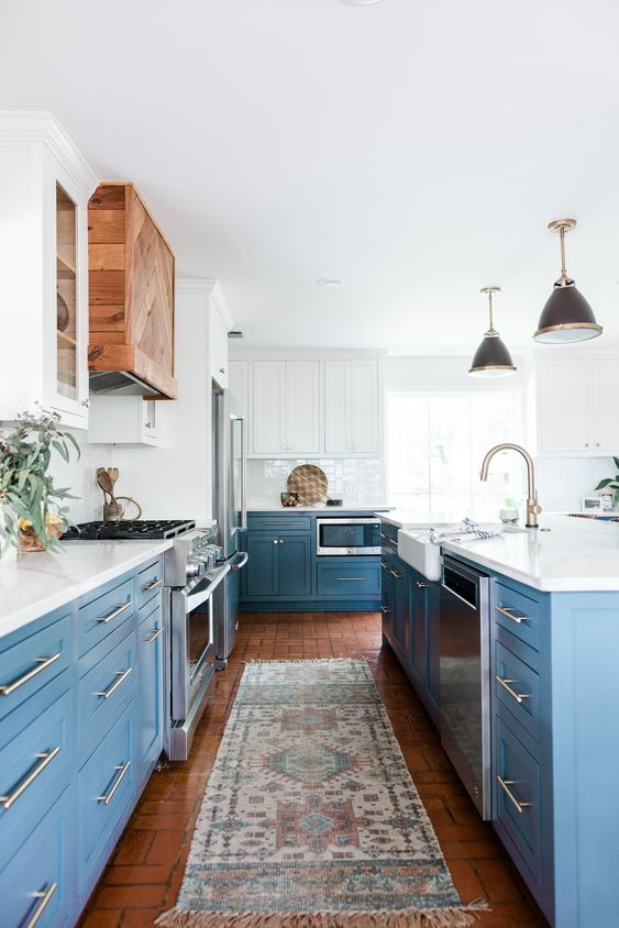 an airy kitchen with white and blue cabinets, white quartz countertops, a white backsplash and stainless steel handles plus a stained wooden hood