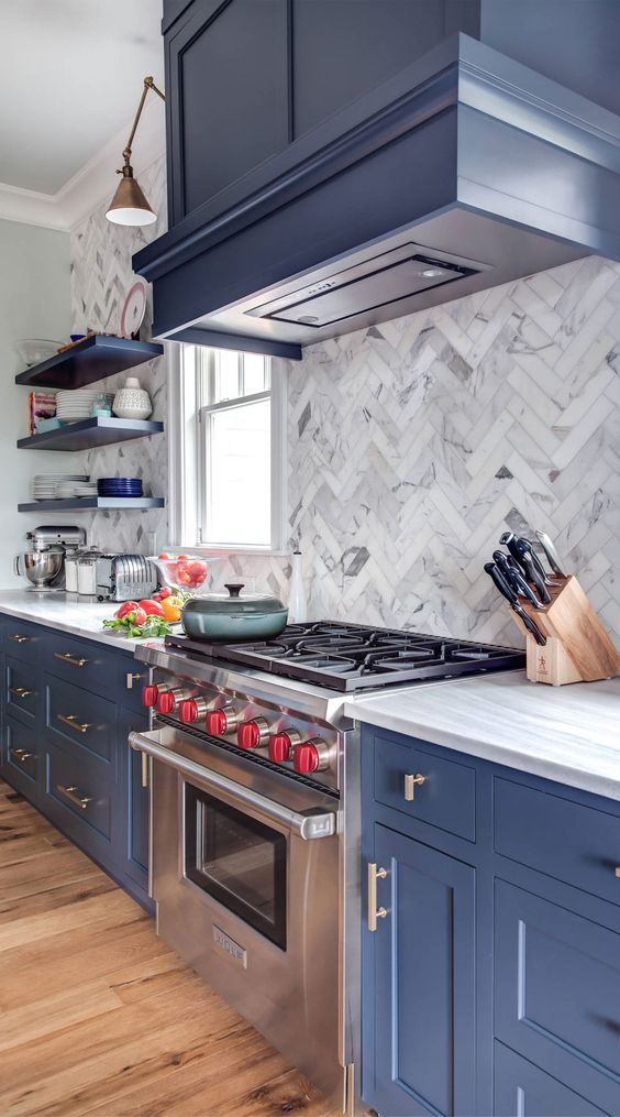 an amazing blue kitchen with shaker style cabinets, a white marble tile backsplash and white quartz countertops plus brass touches