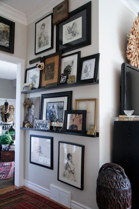 an awkward nook with black ledges and various colored and black and white art in black frames and some more art hanging over the ledges