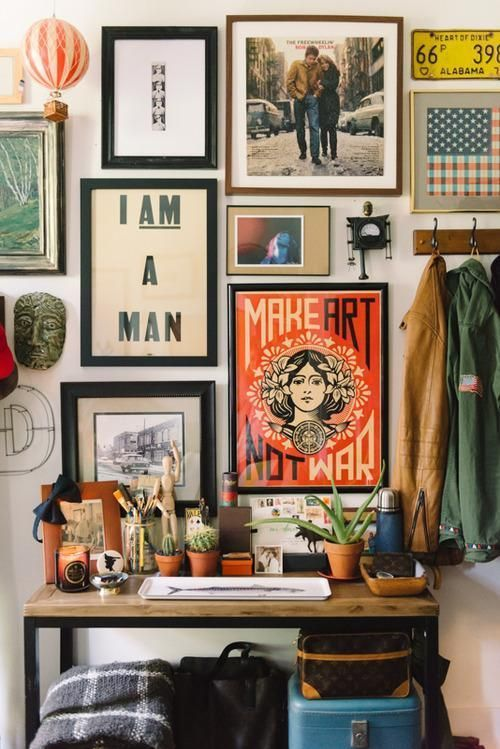 an eclectic gallery wall with various art and mismatching frames plus some pretty souvenirs is very cool