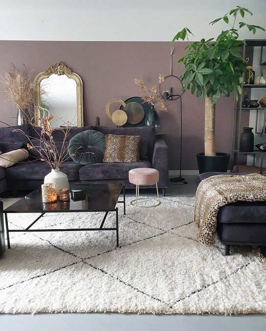 an eclectic living room with mauve walls, dark furniture, potted plants and grasses plus a mirror in a vintage gold frame