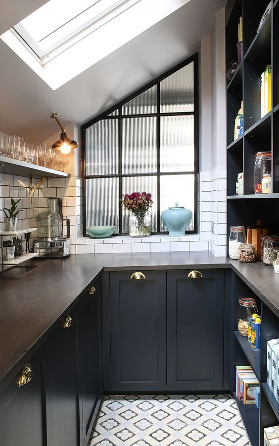 an elegant black U-shaped kitchen with butcherblock countertops and a white tile backsplash is chic