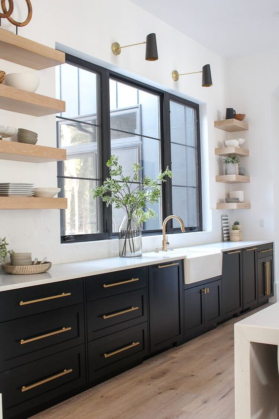 an elegant black farmhouse kitchen with open floating shelves, a white backsplash and countertop plus brass touches