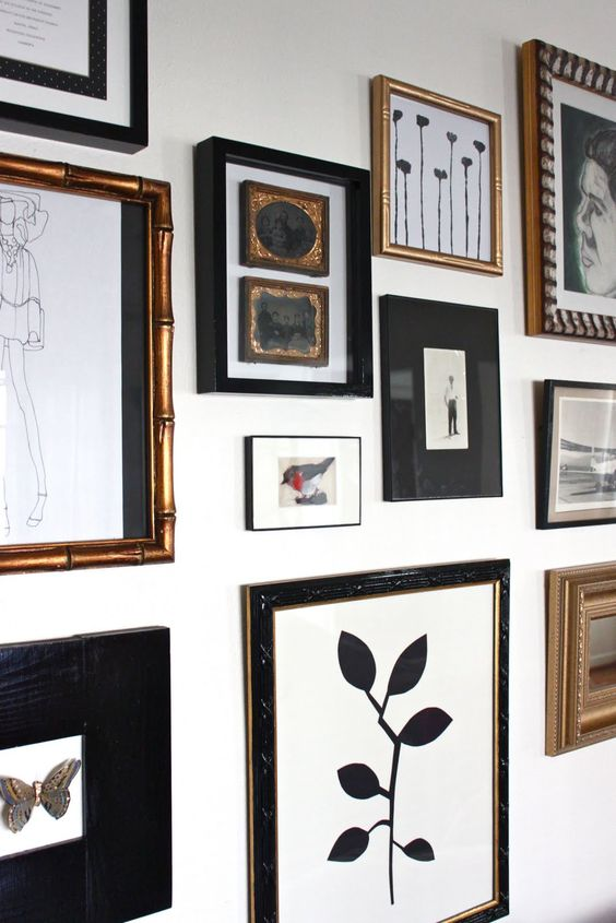 an elegant free form gallery wall with gold and black frames and black and white artworks is very chic