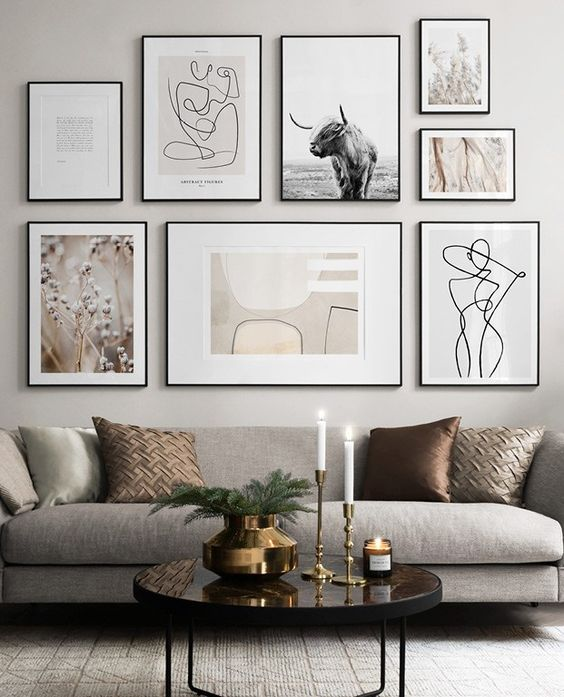 an elegant free form gallery wall with thin black frames and white mats plus muted color and black and white art