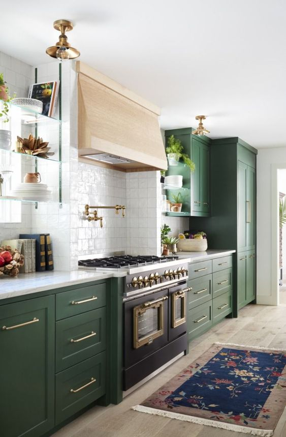 an elegant green kitchen with a blonde wood hood and a vintage cooker plus brass lamps and white countertops