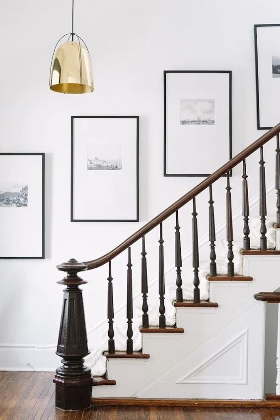 an elegant grid gallery wall with black and white artworks, matting and black frames is a super stylish idea