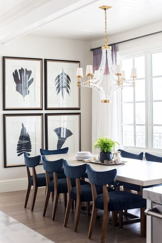 an elegant grid gallery wall with dark frames and silhouette prints is a great addition to this modern dining zone