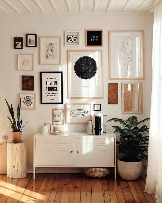 an elegant modern gallery wall with blakc and blonde wood frames, with black, white and brown artworks