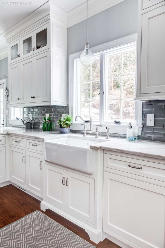 an elegant vintage white kitchen with shaker cabinets, white quartz countertops, a grey glossy tile backsplash and stainless steel touches