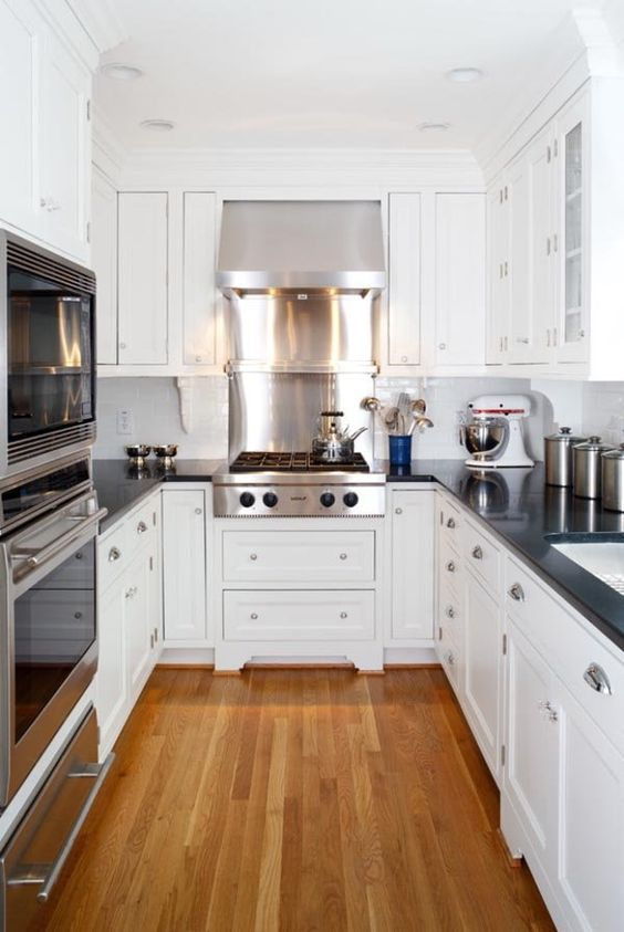 an elegant white U-shaped kitchen with black coutnertops and a white tile backsplash plus shiny appliances