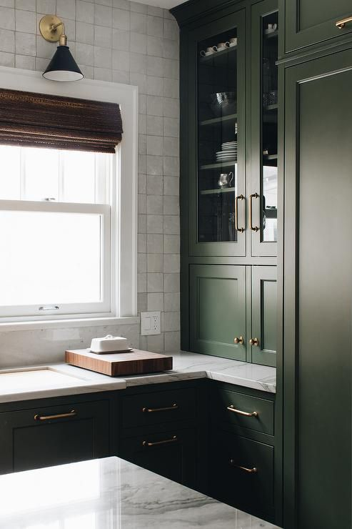 an exquisite dark green kitchen with shaker style cabinets, a white square tile backsplash and white quartz countertops plus a retro lamp
