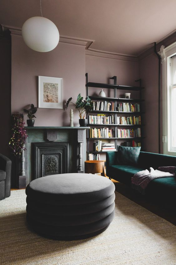 an exquisite living room with mauve walls and a ceiling, open shelves, a green sofa, a non-working fireplace and potted plants