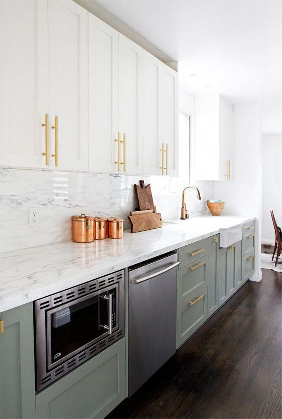 an exquisite two tone kitchen with white and sage green cabinets, a white quartz backsplash and countertops plus touches of gold