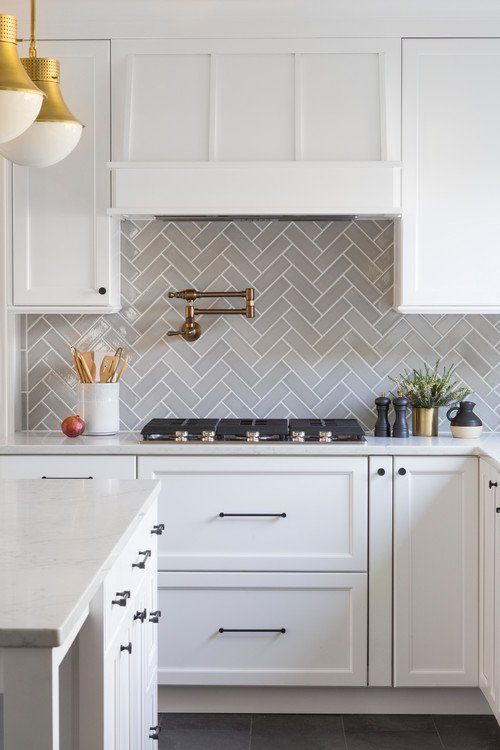 an exquisite white kitchen with shaker cabinets, white quartz countertops, a grey herringbone tile backsplash and touches of gold and brass