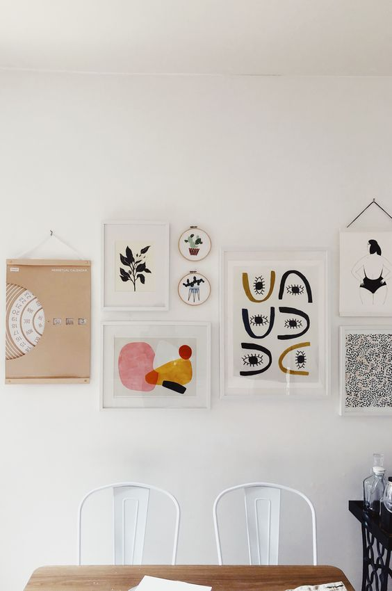 an eye-catchy gallery wall with white and blonde wood frames, with bold graphic artworks is chic and cool