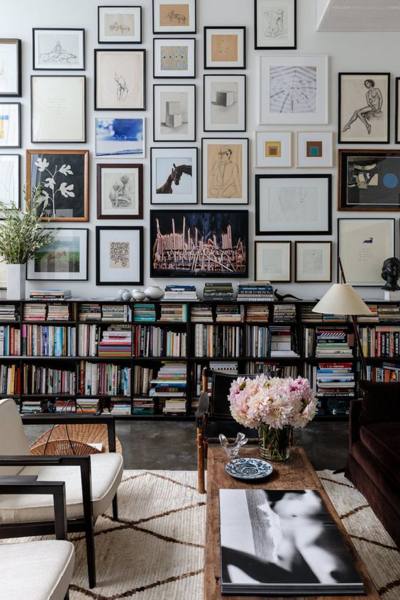 an oversized gallery wall that takes the whole wall and shows off mismatching artworks and frames is all chic
