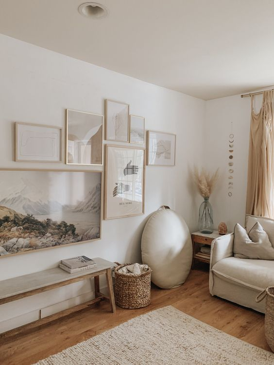 en ethereal free form gallery wall with thin blonde wood frames and pale and muted color artworks looks very cohesive