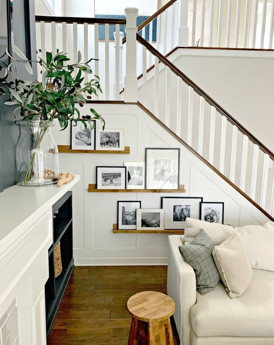 stained ledges with black and white artworks and black and white frames are amazing to style the staircase