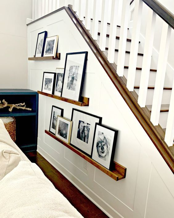 stained ledges with black and white family pics in mismatching frames to style the staircase a bit