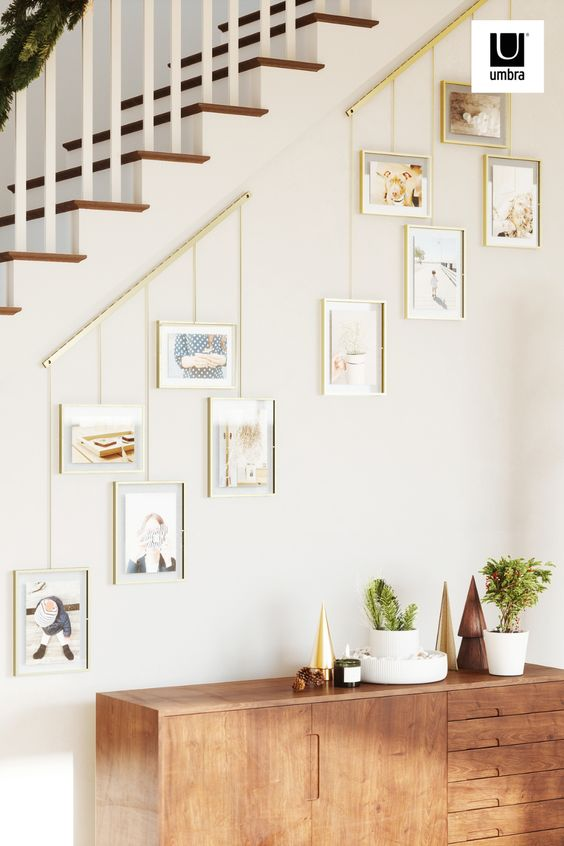 wall-mounted brushed metal ledge with clips and brackets to hold five gallery-style picture frames of various size