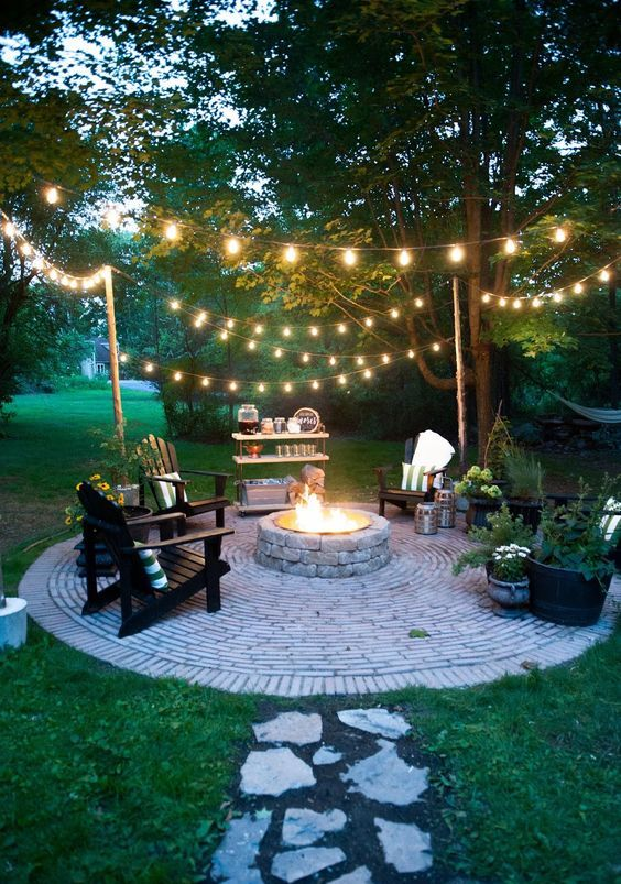a backyard fire pit with string lights over the space is warm and welcoming and looks very cool