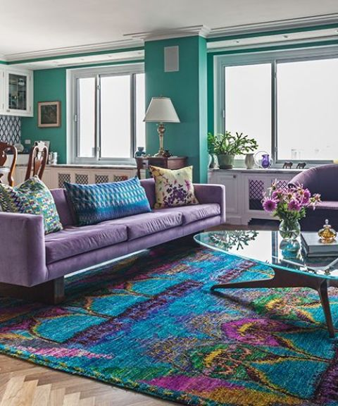 a bright living room with green walls, a purple sofa and chairs, a bright rug with purple touches and a glass coffee table