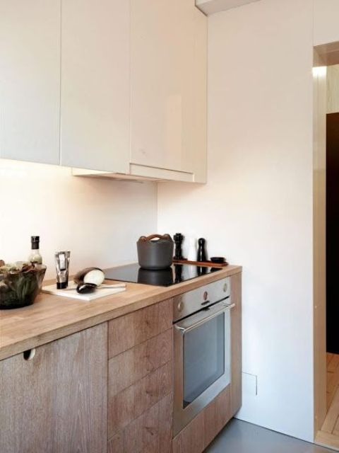 a contemporary kitchen with light stained lower cabinets and sleek white upper ones plus a hood is a stylish and chic space