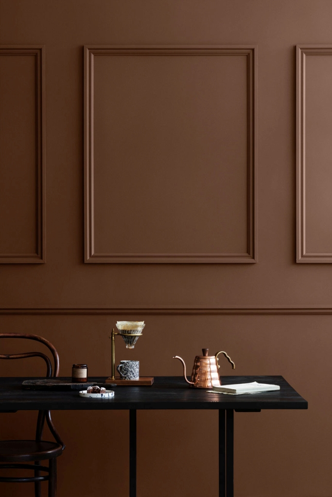 a vintage minimalist space with chocolate brown paneled walls, dark and black furniture is a lovely way to introduce some color
