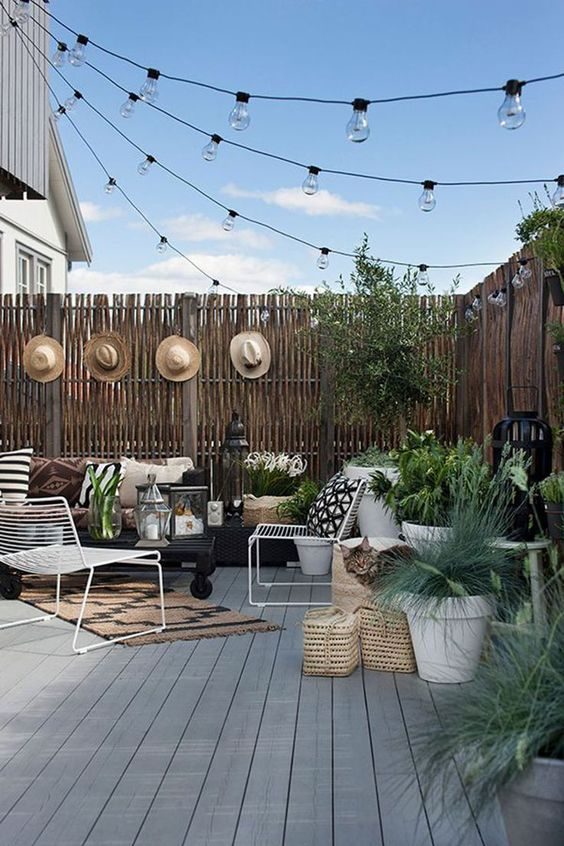 a backyard deck styled with string lights over the space and some candle lanterns on the deck is very welcoming and chic