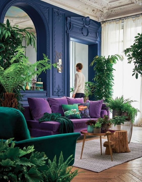 a bright living room with bold blue walls, a purple sofa, an emerald chair, potted greenery and a large mirror