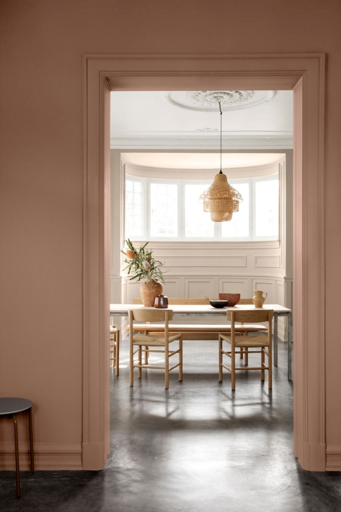 a chic minimal space with a blush wall and doorway to frame a view of the dining space