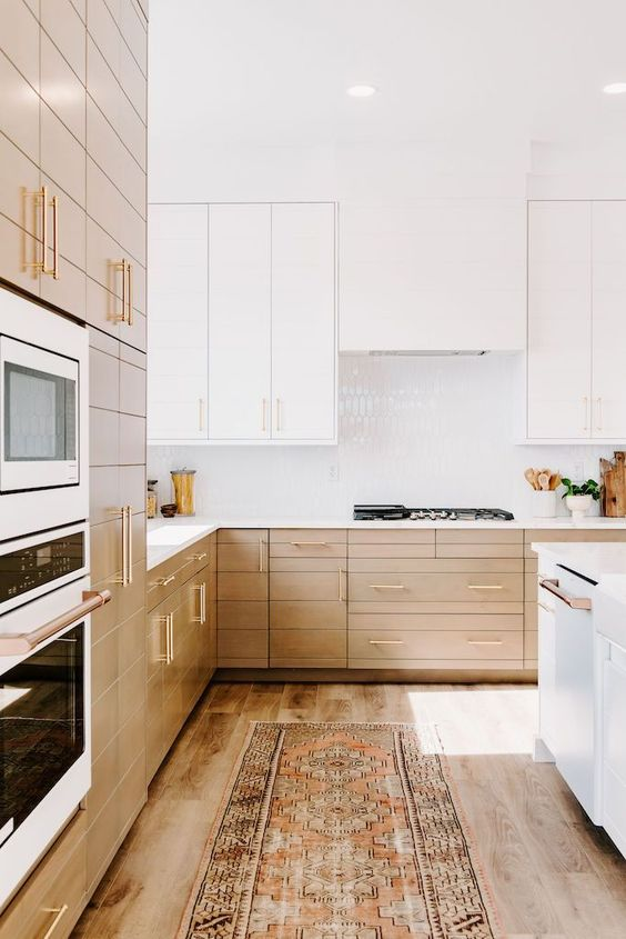 a contemporary kitchen with light stained lower cabinets and white upper ones and a seamless hood and white a glossy tile backsplash