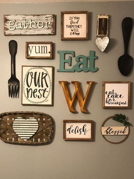 a lovely kitchen gallery wall with letters and monograms, signs in frames, pretty cutlery and a tiny wreath with greenery