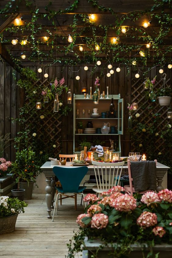a backyard dining space with string lights over the space and candle lanterns on the table plus florals around