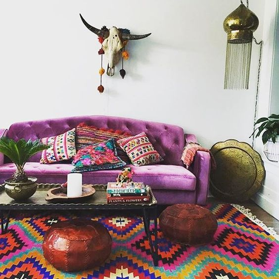 a colorful boho living room with a purple sofa, a colorful rug, bown poufs, a low table, a skull and a pendant lamp
