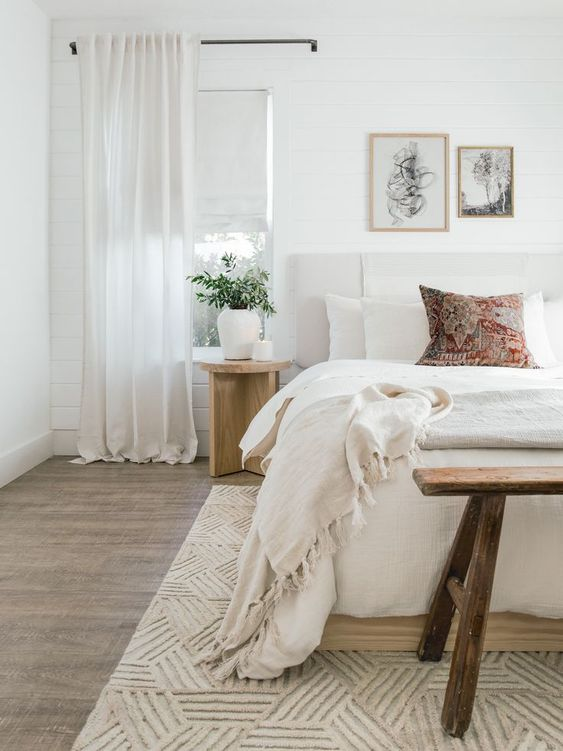 a neutral bedroom with an upholstered bed, a wooden bench and nightstands, neutral textiles and lovely artworks