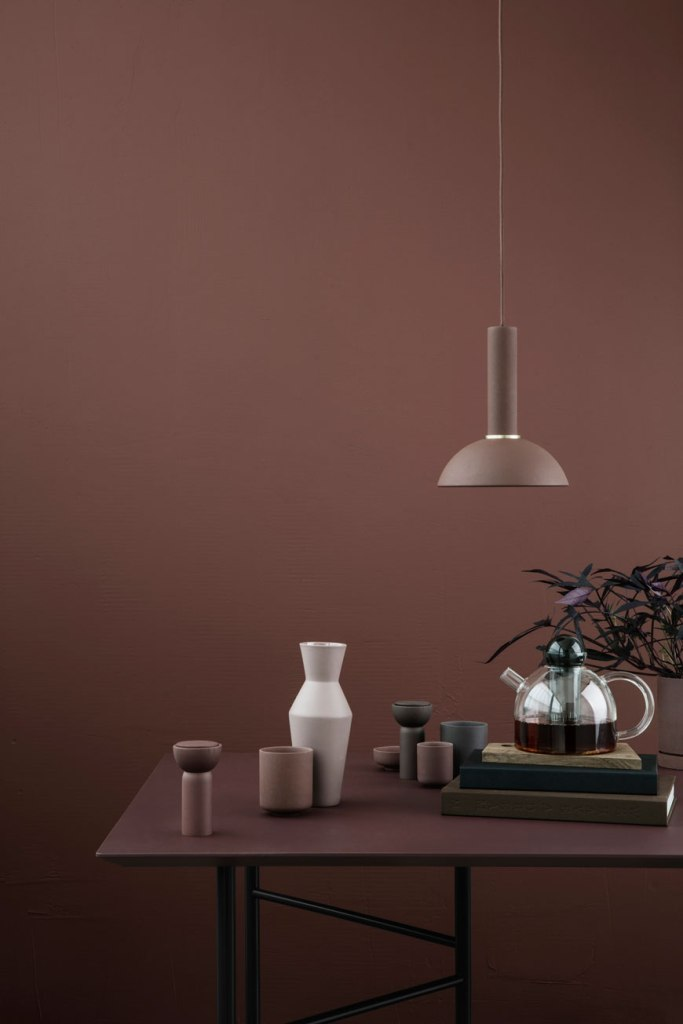 a stylish minimal space with a mauve wall and a matching mauve table, a taupe pendant lamp and porcelain
